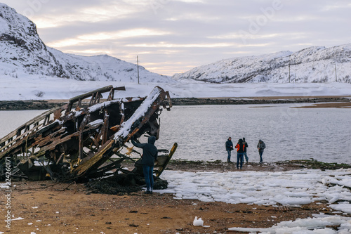 Spoed Fotobehang Poolcirkel People and abandoned ship in Teriberka, Murmansk Region, Russia