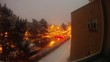 Timelapse out an apartment window of cars during a snowstorm at night.