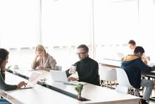 Group Of People Working At Desks In Big Modern Workspace, Copy Space