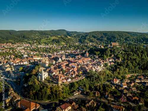 Fotografia, Obraz  Aerial panorama of medieval Sighisoara in Romania with blue sky, red roofs, bast