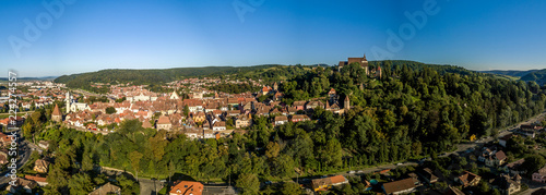 Fotografie, Obraz  Aerial panorama of medieval Sighisoara in Romania with blue sky, red roofs, bast