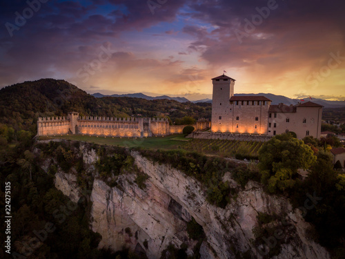 Fotografie, Obraz  Medieval castle in Angera Italy with dramatic purple, red, yellow sky