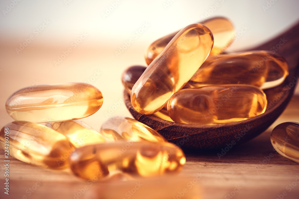 Fototapeta Close up the vitamin D and Omega 3 fish oil capsules supplement on wooden plate for good brain , heart and health eating benefit