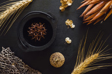Black Cauldron With Sycamore Pod And Dried Wheat, Seeds And Flowers