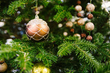 Closeup Of Gold Bauble Hanging From A Decorated Christmas Tree. Bauble Hanging From A Decorated Christmas Tree.