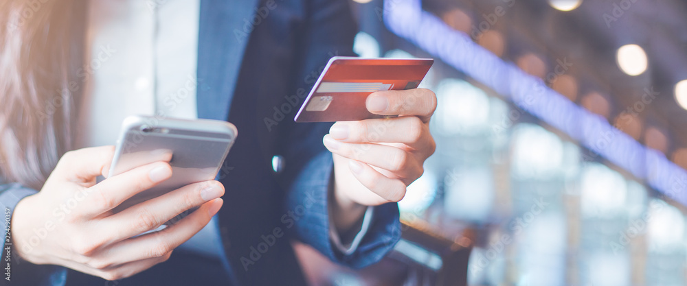 Fototapeta Business woman hand use credit cards and smartphones.Web banner.