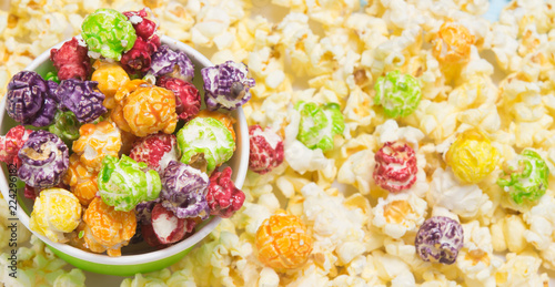 a sweet, colorful popcorn lies in a bucket and is scattered on the table