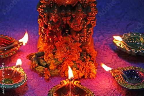 god laxmi and ganesha worshiping with clay lamp diya on diwali festival