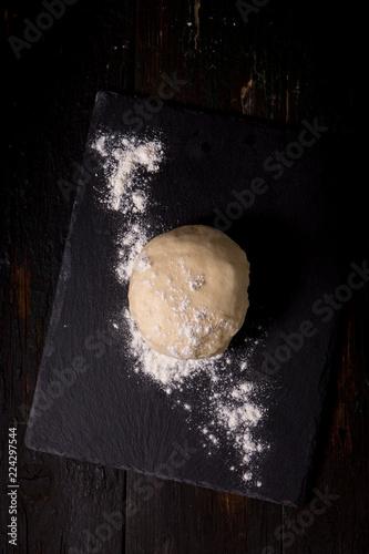 Fototapeta Dough with flour on a black board, top view obraz
