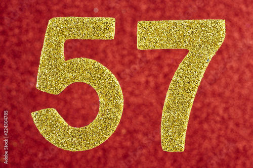 Fotografie, Obraz  Number fifty-seven gold color over a red background. Anniversary