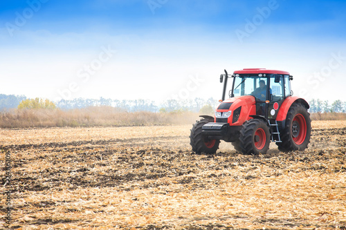 Modern red tractor working on the field