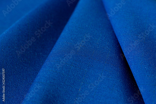 Poster Tissu Texture of fabric and folds. A blue gabardine fabric creates a background. Fabric for sewing fashionable and stylish clothes.