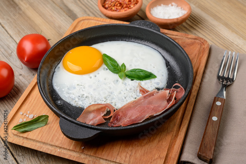 Fried egg in a pan with bacon and tomatoes on rustic wooden background.