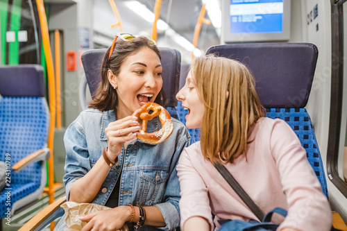 woman eating pretzel while traveling by train
