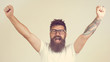 Lucky young hipster man isolated over grey background. Bearded man wearing glasses acts like he won something with copy space. Good advertising of your products, autumn sale, discount, Black Friday.