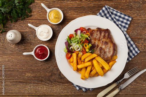 Grilled pork neck served with French fries and salad.