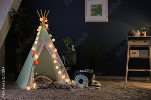 Cozy play tent for kids with glowing garland in room interior Canvas