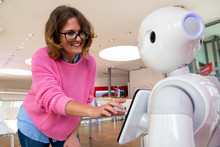 A Woman Communicates With A Robot Consultant