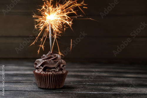 Photo  Tasty chocolate cupcake with sparkler on wooden table