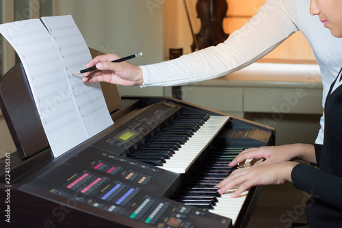 Fotografía  Young artist musician woman learn to play piano, practice and train skills, teacher compose writing notes by pencil