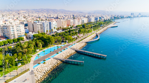 Spoed Foto op Canvas Cyprus Aerial view of Molos Promenade park on coast of Limassol city centre,Cyprus. Bird's eye view of the jetty, beachfront walk path, palm trees, Mediterranean sea, piers, urban skyline and port from above