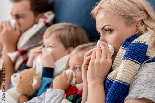 Fotografia, Obraz  close-up shot of sick young family blowing noses with napkins together while lyi