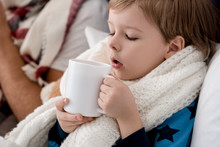 Close-up Portrait Of Little Kid In Scarf With Cup Of Hot Drink Sitting In Bed