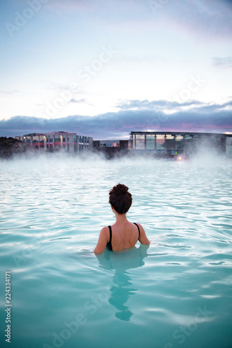 Spoed Fotobehang Europa Woman relaxes and enjoys of spa in hot spring Blue Lagoon in Ice