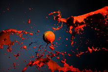 Red Paint Splash And Tennis Ball On Blue Background