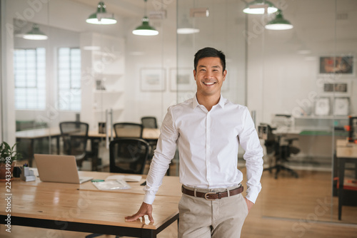 Foto  Young Asian businessman standing in an office smiling confidently