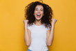 Image of young woman 20s with curly hair yelling and clenching fists, isolated over yellow background