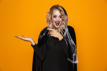 Frightening Woman Wearing Black Costume And Halloween Makeup Holding Copyspace On Palm, Isolated Over Yellow Background