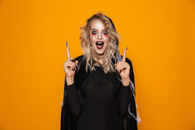 Amazing Woman 20s Wearing Black Costume And Halloween Makeup Pointing Fingers Upward, Isolated Over Yellow Background