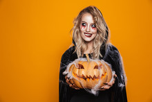 European Witch Woman Wearing Black Costume And Halloween Makeup Holding Carved Pumpkin, Isolated Over Yellow Background