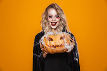 Dangerous Woman Wearing Black Costume And Halloween Makeup Holding Carved Pumpkin, Isolated Over Yellow Background