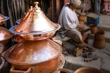 Copper Pans Stacked In The Foreground With A Copper Artisan Shown Working And Building The Product By Hand In The Background