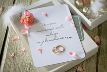 Two Golden Wedding Rings, Box Of Chocolates And A Wedding Invitation, An Inscription That The Story Of True Love Never Ends. Copy Space.