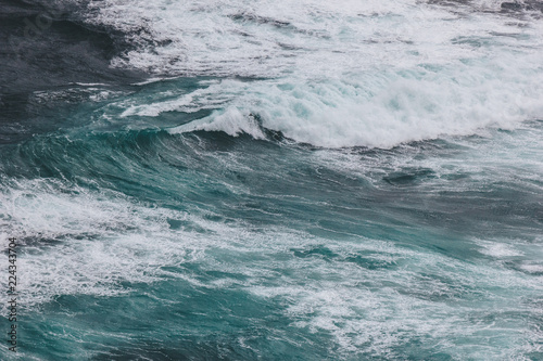 aerial shot of blue ocean with foamy waves for background