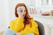Leinwandbild Motiv redhead woman looking through paper telescope