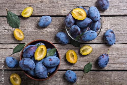 Photo Fresh plums in bowl on wooden table