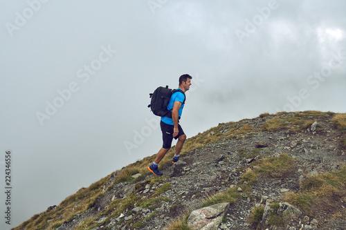 Fototapeta Hiker with backpack in the mountains obraz na płótnie