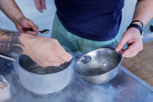 Unusual Dishes. Tattooed Man Mixing Ingredients While Cooking Something Unusual