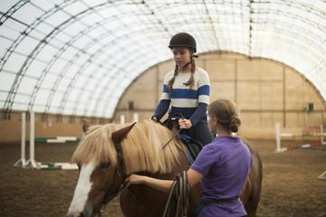Teen girl in helmet learning Horseback Riding