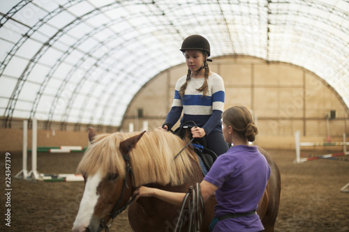 Photo Stands Horseback riding Teen girl in helmet learning Horseback Riding