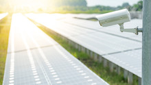 CCTV Camera Monitoring Solar Panels Or Polycrystalline Silicon Solar Cells In The Farm. Security In Solar Power Plant. Photovoltaic Modules For Renewable Energy