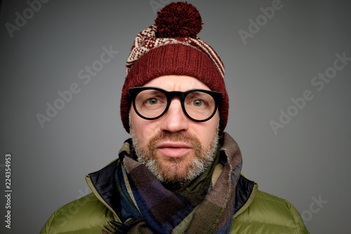 Fotografía  Close up portrait of middle aged europeam man in funny warm hat and glasses noticing hidden camera