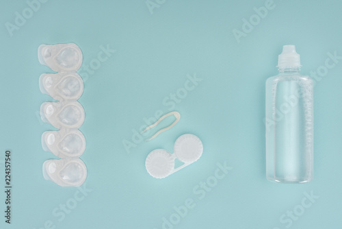 Fotografia  flat lay with sterile liquid in bottle, tweezers and containers for contact lens