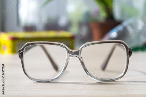 Glasses for vision on the table. Wallpaper Mural