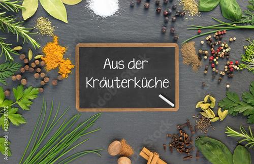 Aus der Kräuterküche - Tafel inmitten diverser Küchengewürze und Kräuter