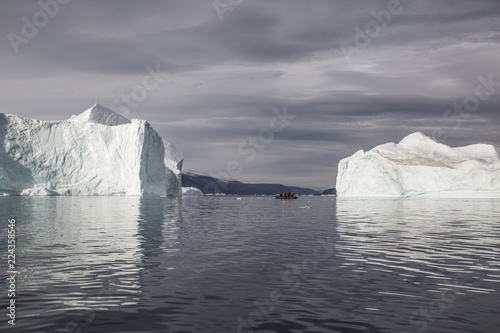 Spoed Fotobehang Poolcirkel rubber dinghy cruising in front of massive Icebergs floating in the fjord scoresby sund, east Greenland